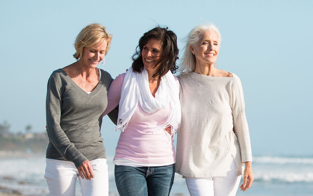 Three women walking closely on the beach.